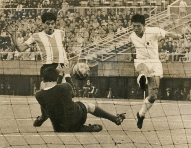 TOKYO, JAPAN - OCTOBER 14:  (CHINA OUT, SOUTH KOREA OUT) Ryuichi Sugiyama of Japan scores his team's first goal during the Tokyo Olympics Football Group D match between Japan and Argentina at Komazawa Stadium on October 14, 1964 in Tokyo, Japan.  (Photo by The Asahi Shimbun via Getty Images)